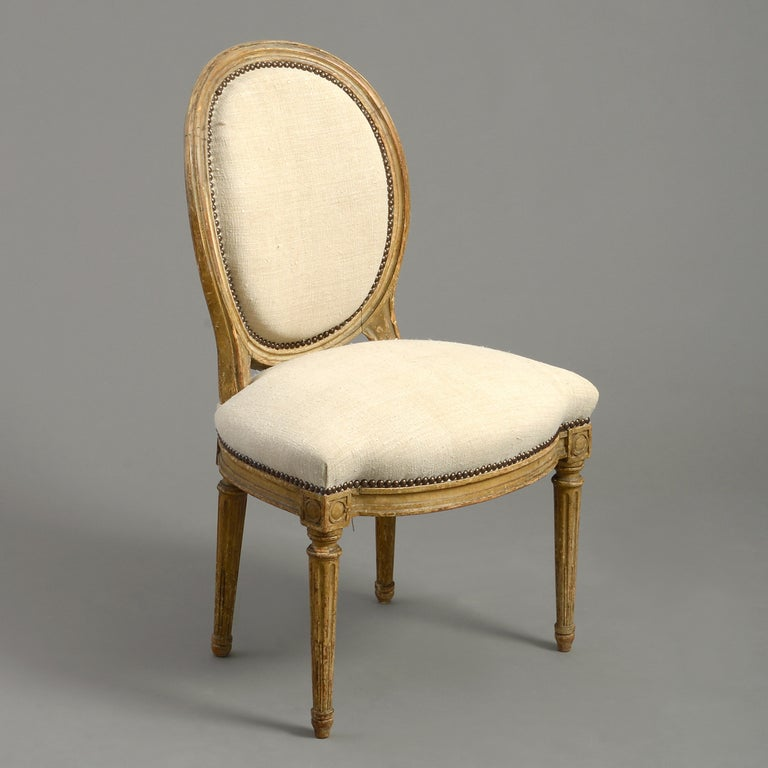 A good pair of late 18th century carved and painted upholstered side chairs, the overstuffed oval backs upon a seat of the safe with close brass nailing. The tapering stop-fluted legs headed by ring paterae.