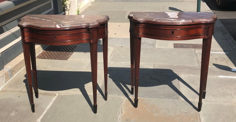 Elegant pair of mahogany neoclassical consoles with marble tops. These Classic consoles are a solid mahogany with a single-drawer. Each console has fluted mahogany legs going down to ebony stop fluting in the center of each flute. The legs are