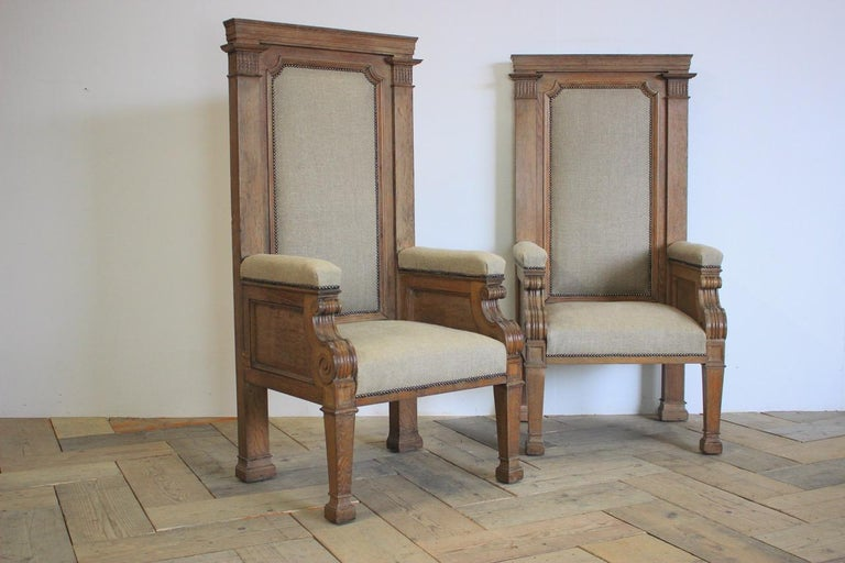 A large pair of late 19th century English armchairs in solid oak, of great proportions, having been reupholstered in neutral linen with studs. Measures: Floor to seat 49cm High.