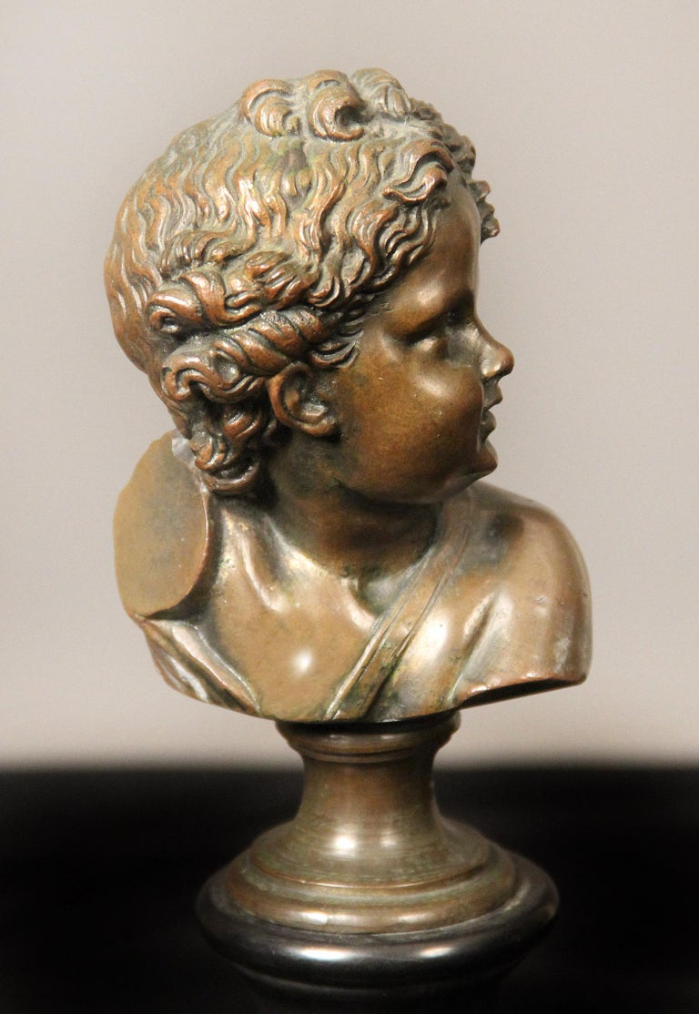 A pair of late 19th century bronze busts  By A. Mahuex  Depicting busts of young boys sitting on a black marble base.