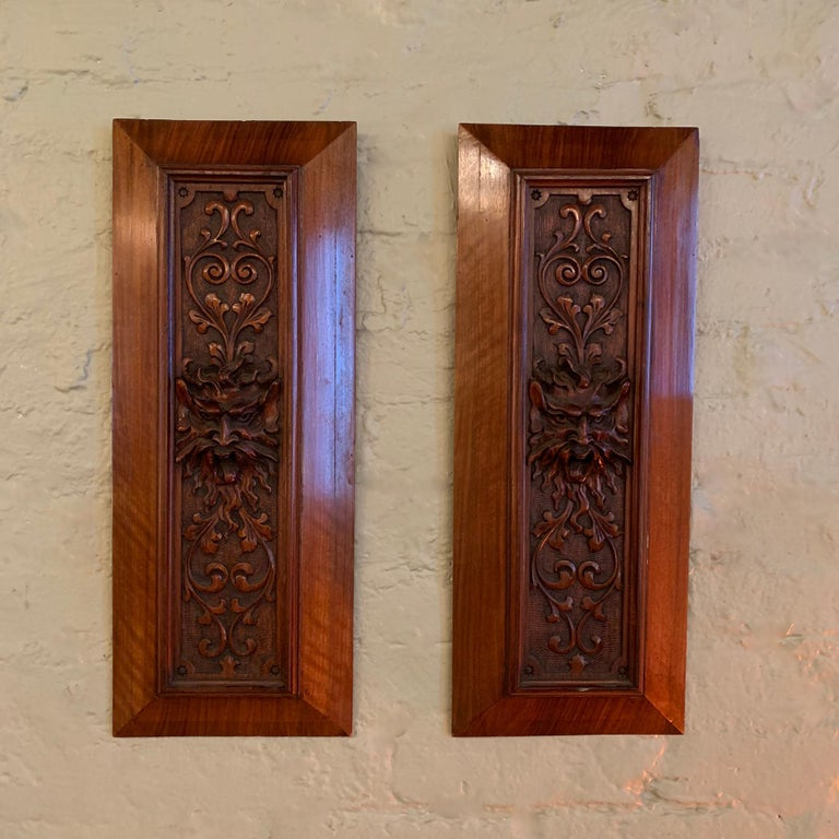 Pair of late 19th Century, relief carved, mahogany panels emanating from a gargoyle head.