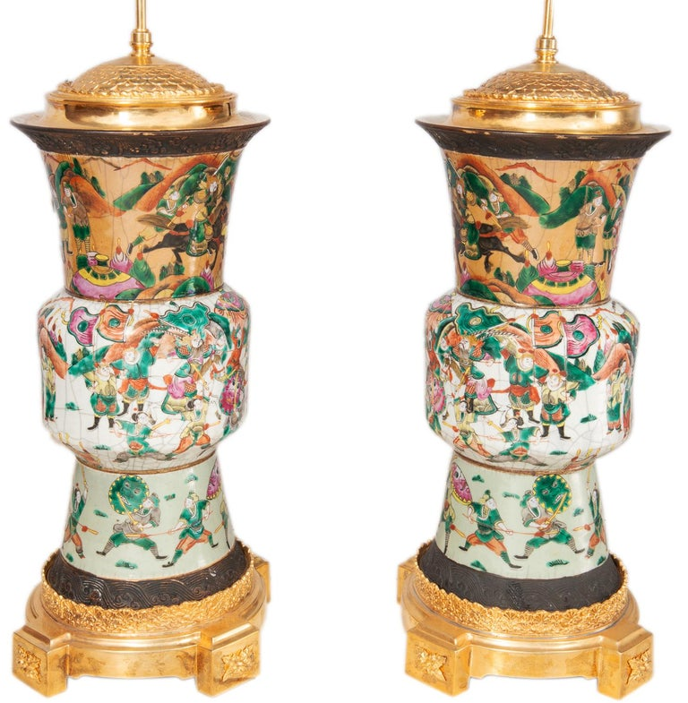 A pair of late 19th century Chinese crackle-ware vases/lamps. Each with various battle scenes with warriors on horseback, mounted with wonderful gilded ormolu lids and bases.