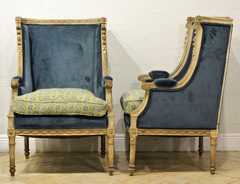 Painted in antique grey/white with small gilt accents and nice wear these well carved bergeres are tastefully complimented by their new cover of blue velvet and matching French pattern cushions.