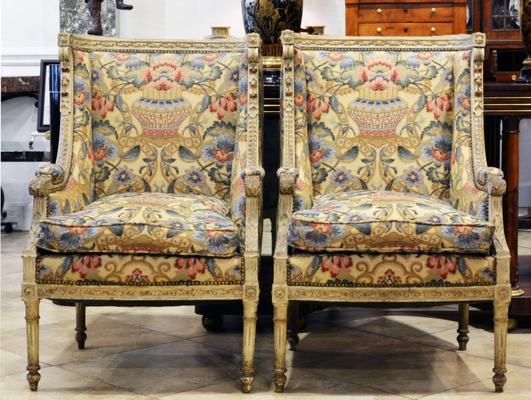 Painted in antique grey/white with small gilt accents and nice wear these well carved bergeres are tastefully complimented by their cover of Aubusson style fabric featuring jardinières, flowers, leaf work and ornamental borders in beautiful subdued