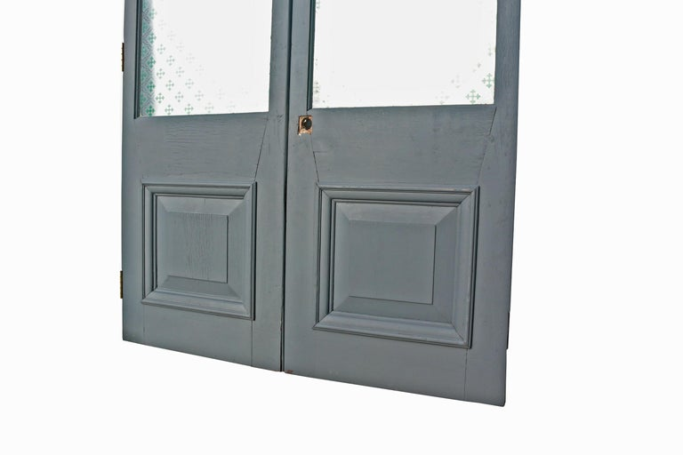 These doors are in good condition for their age.  They are not rebated, they were previously used as swing doors and have a rounded inner edge. Original patterned glass. Painted with grey primer.   Measures: Height 210 cm  Width 134
