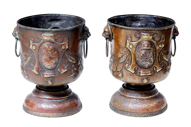 Pair of continental copper wine coolers or small jardinières, circa 1890.  Made using the repoussé technique. Decorated with armorial cartouches. Cup shape with lion mask ringed handles to the sides, standing on a domed base.  Rubbing to patina