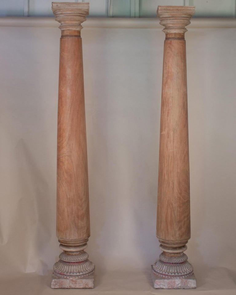 An impressive pair of late 19th century satinwood columns/pillars and capitals with stone bases from Portuguese Goa. The matte satinwood has a beautiful tone and grain, and the bases have retained traces of their original paint.