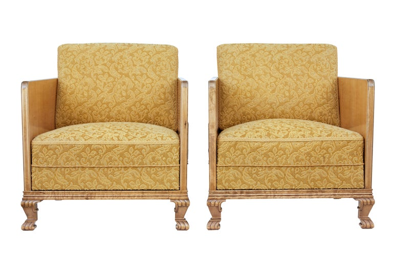 Fine quality pair of Scandinavian elm armchairs, circa 1940.  Thin elm side frame with mahogany stringing and contrasting walnut detail, complete with applied stained birch motif. Standing on front carved paw feet.  Original upholstery is in