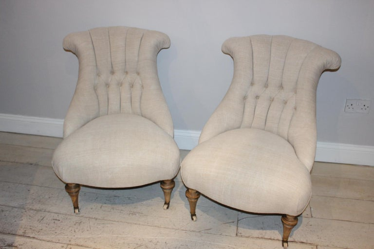 Pair of button-back upholstered late circa 19th century Swedish chairs. A pair lovely salon chairs sit on turned beech legs and have been reupholstered in a neutral French linen to the front and hessian to the back with feature flat piping. These