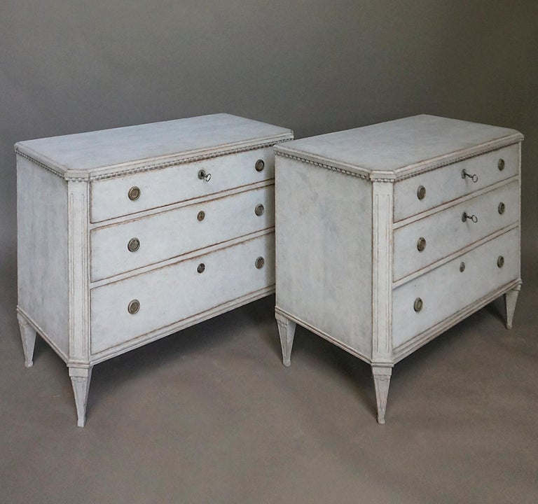 Pair of Gustavian style commodes with three graduated drawers, Sweden, circa 1890. Shaped tops with dentil detail and canted corner posts over tapering square legs.