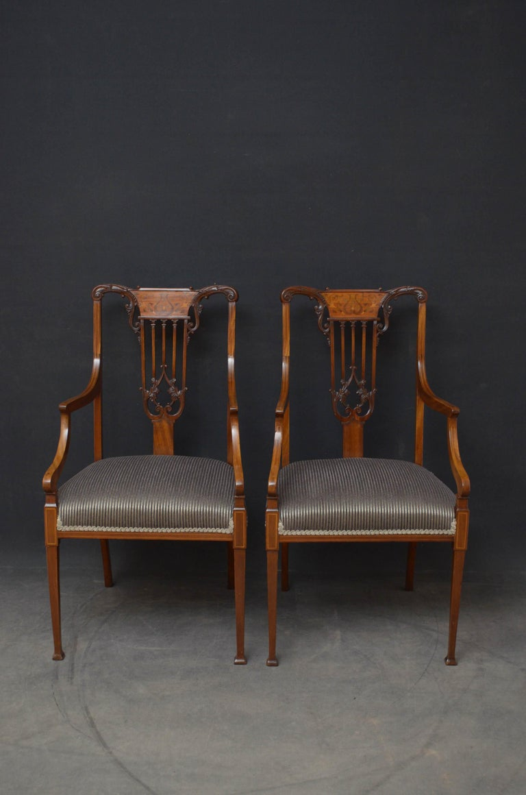 Sn4794 Superb pair of mahogany elbow chairs, each having finely carved rail with inlaid splat and carved slats above newly covered overstuffed seat and satinwood string inlaid open arms, standing on tapered legs terminating in pad feet. This pair of
