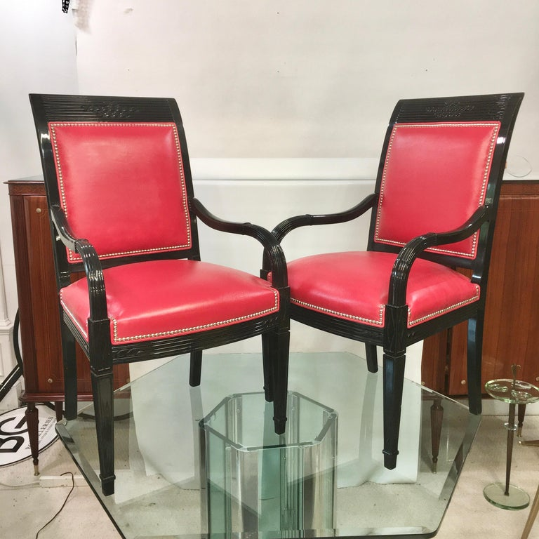 Pair of Art Deco style black lacquered armchairs with red leather upholstery and nickel plated brass nailheads.  Arm height 25 inches.