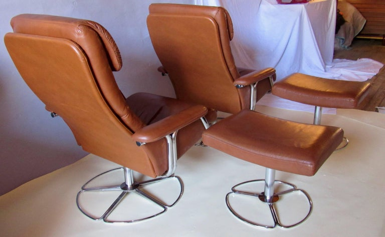 A rare pair of Bruno Mathsson for DUX of Sweden leather and chrome swivel lounge chairs and ottomans imported by Finmark, Inc. According to Pamono and 1stdibs this is a DUX product designed by Bruno Matsson.   Labeled