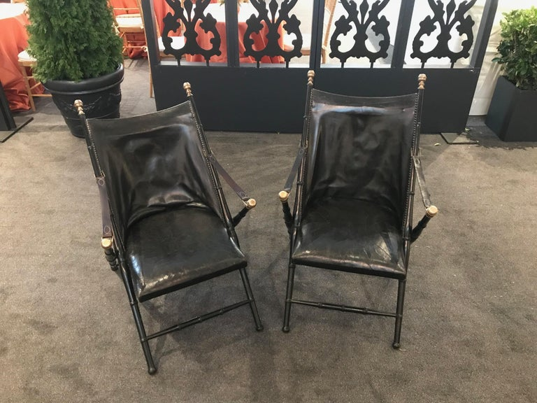 Pair of leather and ebonized pear wood folding chairs by Maison Jansen.