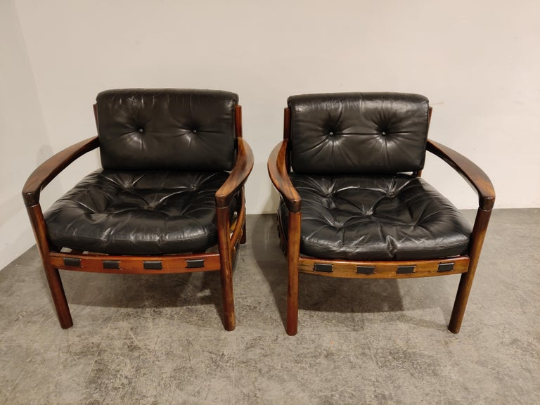 Pair of leather amrchairs design by Sven Ellekaer for Coja Culemborg.  Beautifully shaped rosewood frame with the original leather cushions.  The cushions/seats are still usable but are worn with some previous repairs.     1960s -