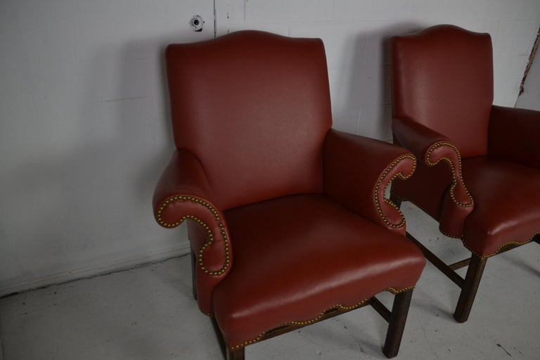A pair of soft leather armchairs in a rust-red color. Scrolled arms and brass stud edging.