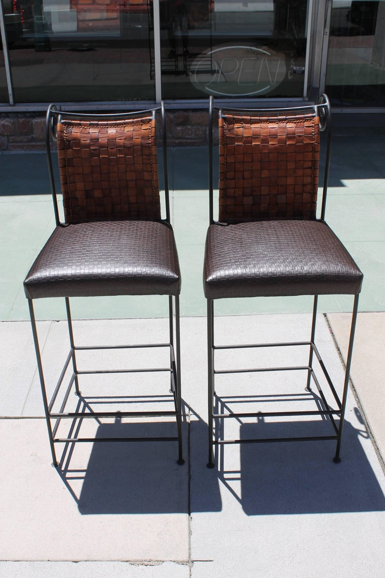 Pair of brown leather spanish barstools. The seat cushion was originally straps of leather similar to the back portion. We decided to reinforce and redo the seat cushion with leather. Notice the pattern is similar to the back portion. They measure