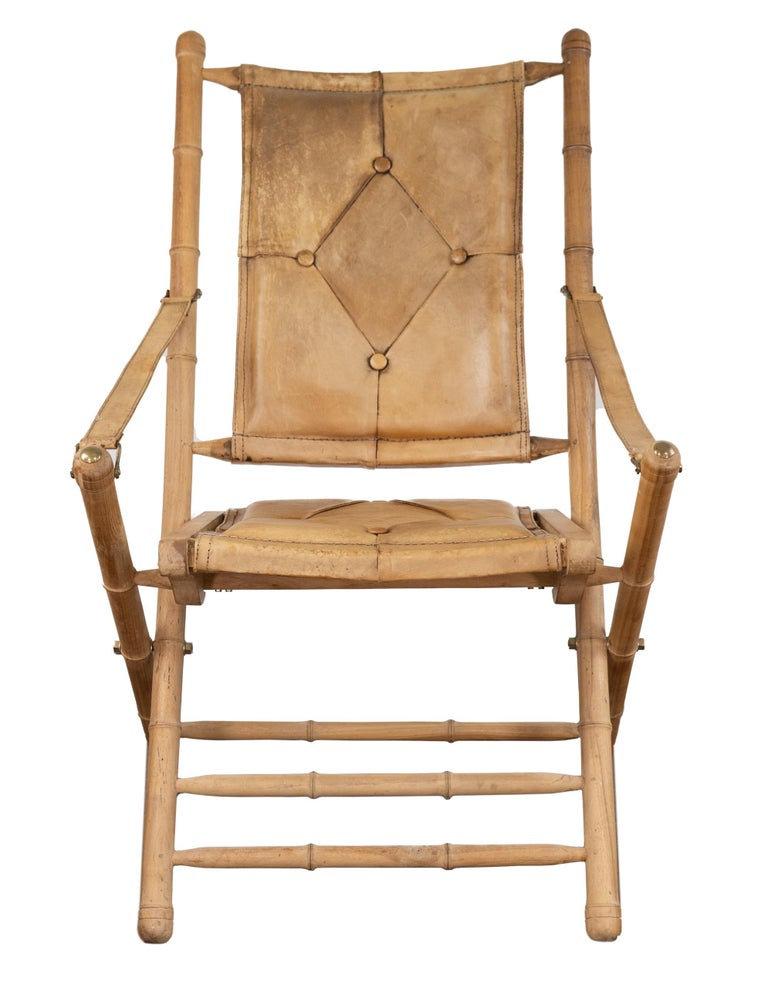 A pair of early 20th century bamboo folding chairs. Seat, backrest, and arm straps all upholstered in distressed camel colored leather with brass joints, seat and back are button tufted. Slight wear but otherwise in wonderful condition.