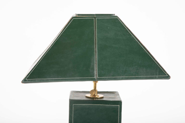 A pair of lamps covered in green leather with white stitching in the manner of Jacques Adnet.
