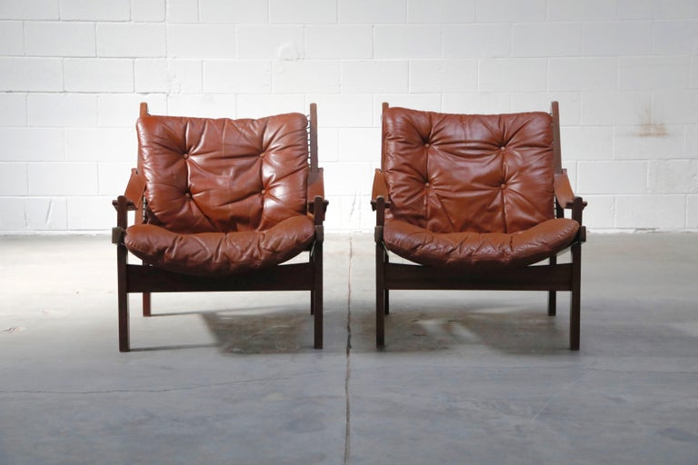 These super cool and laid back pair of leather 'Hunter' safari easy chairs are by Torbjørn Afdal for Bruksbo, 1960s, Sweden. Rare to find in the US, these Scandinavian Modern lounge chairs are the perfect option for someone who wants rare