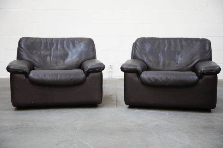 A pair of incredibly laid-back and comfortable De Sede leather club chairs in an attractive high quality deep colored leather, designed and produced in the 1960s in Switzerland. The design features clever lines and shapes, making this work well in a