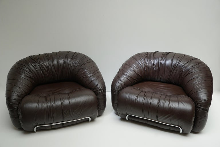 Two lounge chairs / club chairs in the style of Gianfranco Frattini. Each lounge chair features the original brown leather upholstery in tubular chrome frames. Manufactured in Italy, circa 1970s.