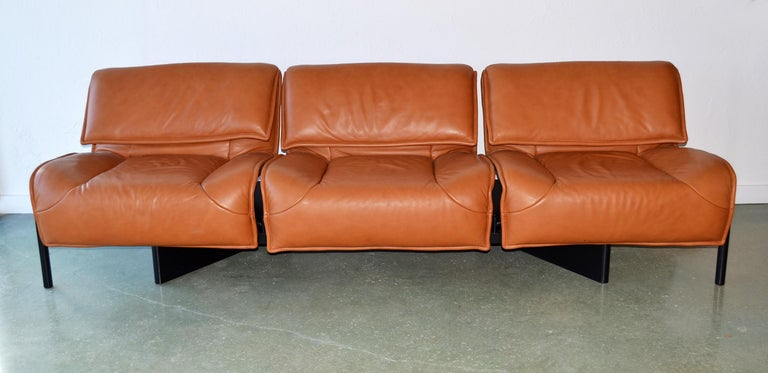Pair of leather sofas or couches by Vico Magistretti for Cassina, Italy, 1980's. (ONE SHOWN) Designed by Vico Magistretti for Cassina, the Veranda sofas feature baseball glove leather with swiveling seats and adjustable headrests and metal legs on a