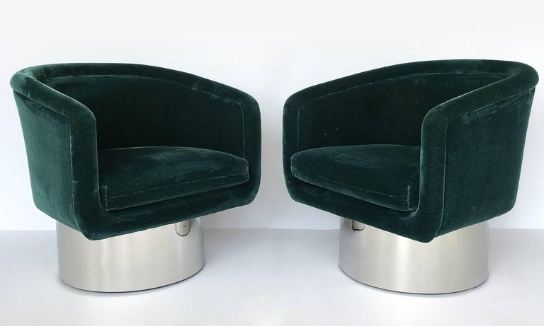 Pair of swivel lounge armchairs with polished steel / chrome pedestal bases by Leon Rosen for Pace, circa 1970s. Upholstered barrel back frames with loose cushion. Mirror polished steel cylindrical pedestal bases. These chairs rotate 180 degrees.