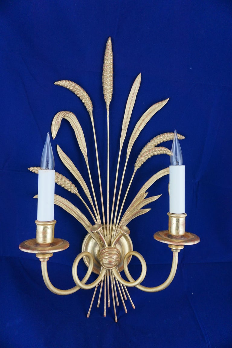 These handed, carved wood and gilded Regency style wheat sheaf wall lights with two lights, were made by the great firm of Leone Cei. Located in the heart of Florence, Italy since 1902, they work in ways that have not changed for over 500 years