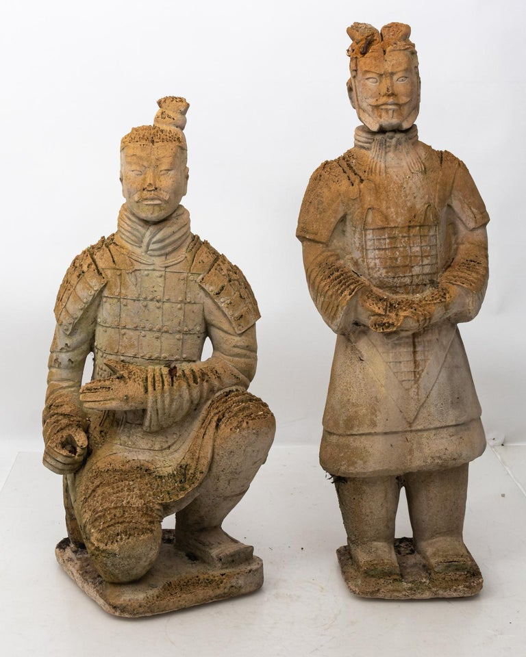 Pair of carved Limestone Japanese warrior statues in a weathered finish. Please note of wear consistent with age and exposure to the elements including loss to limestone and aged moss. The standing figure measures 42.00 inches height by 13.00 inches
