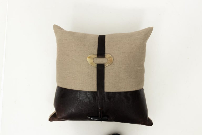 Pair of beige and brown throw pillows with embossed faux leather and faux bone trim. Feather and down inserts.