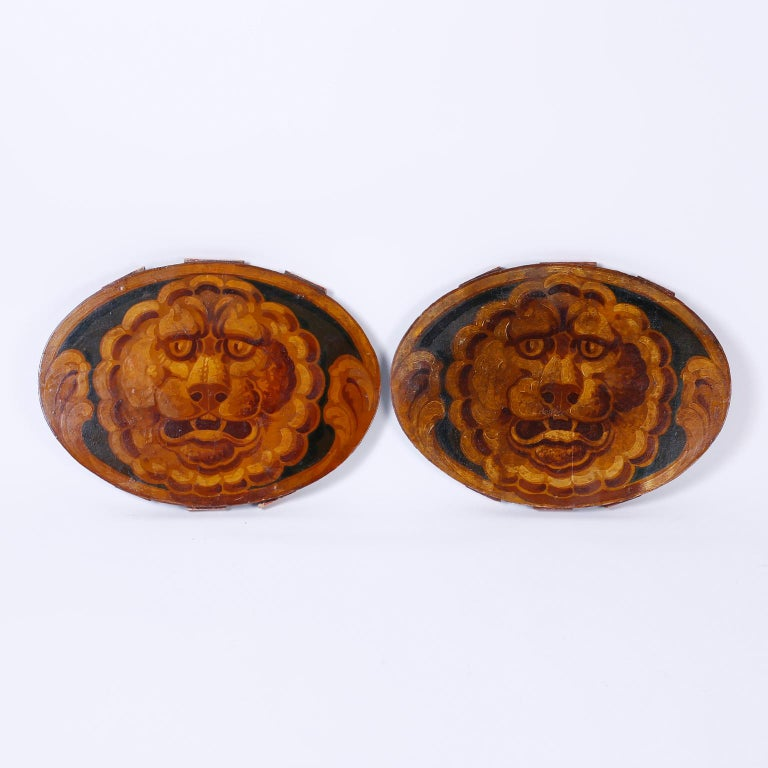 Pair of antique oil on board oval panels portraying folky whimsical lion heads. These panels are architectural remnants possible from a circus car.