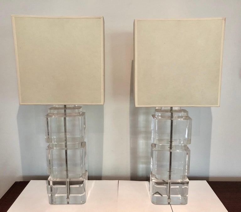 Two large Lucite column table lamps composed of three stacked rectangular blocks with nickel fittings and original parchment shades, circa 1970s.