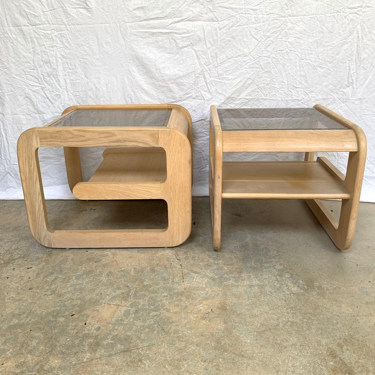 Sculptural pair of organic California modern end or side tables rendered in an original bleached white oak finish with smoked beveled glass tops and in internal oak shelf designed by Lou Hodges, California, USA, 1970s.