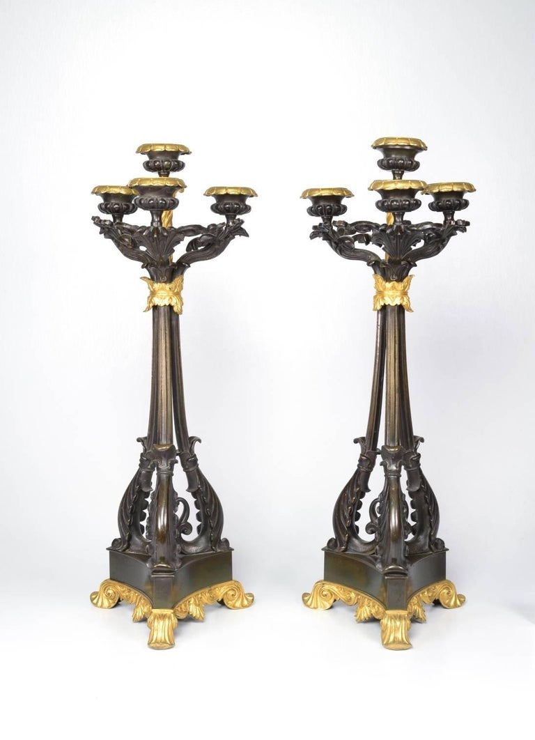 Pair of bronze and ormolu (bronze doré) four-light candlesticks, each with gold floral bobeches and leafy arms raised on three scrolling branches bundled at the top; the triangular base raised on doré feet.