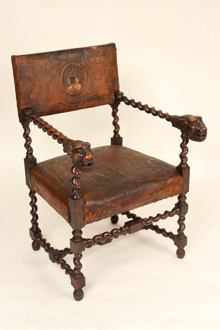 Pair of Louis XIII style armchairs with great lion carved arms and old embossed leather upholstery, circa 1890-1910. The lion carving on these chairs have great character, quality and old excellent color. The leather is embossed with floral and