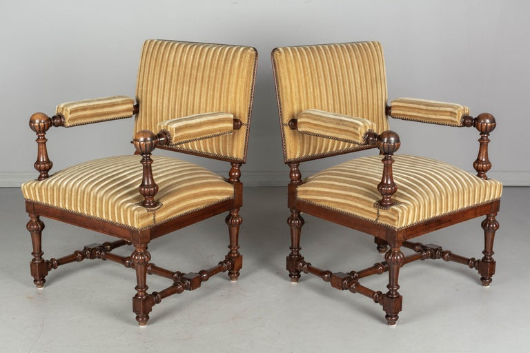 A pair of Louis XIV style French fauteuils, or arm chairs, with solid walnut frames. Boldly carved armrests with large ball finials and turned wood spindle legs and stretcher. Nice proportions with square profile, sturdy construction and comfortable