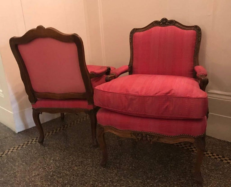 Fabulous pair of Louis XV beechwood Fautueils à la Reine. Made by Pierre Leduc, circa 1750s. These chairs were in the NYC home of Greta Garbo in the star's living room!   Each chair backseat displays a berried fruit-and foliate-carved cresting,