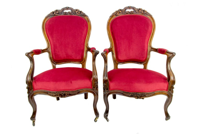 Pair of Louis XV style armchairs or fauteuils from the late 19th century is made of walnut wood, with an upholstered seat, armrests and a backrest, decorated with beautiful floral carvings. The front legs of the armchairs are cabriole, on rollers.