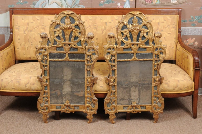 A pair of 19th century French Louis XV style giltwood mirrors featuring carved fruit baskets, grapevines and foliate scrolls mounted to mirror plates. The mirrors with oak back boards.