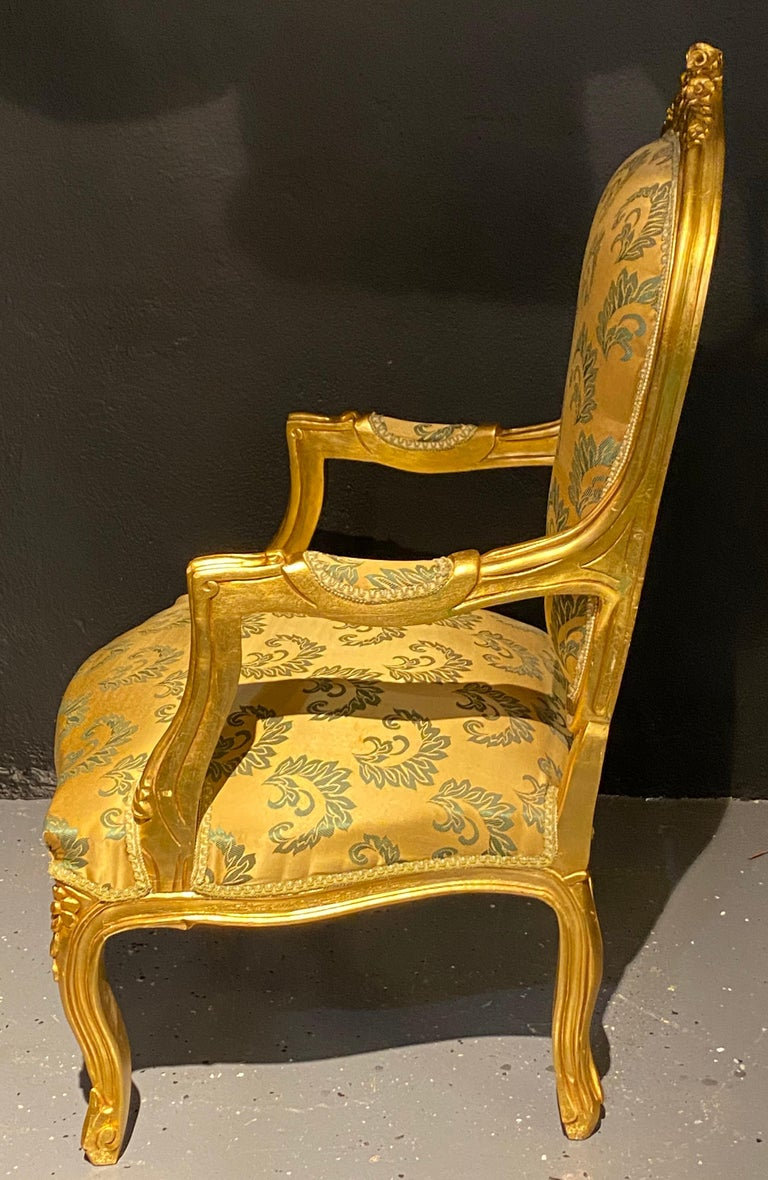 Pair of Louis XV style giltwood fauteuils or armchairs. This stunning pair of gilt gold Fauteuil chairs are covered in a satin Scalamandre upholstery reminiscent of the early French era of opulence. Each strong and sturdy frame having roses carved