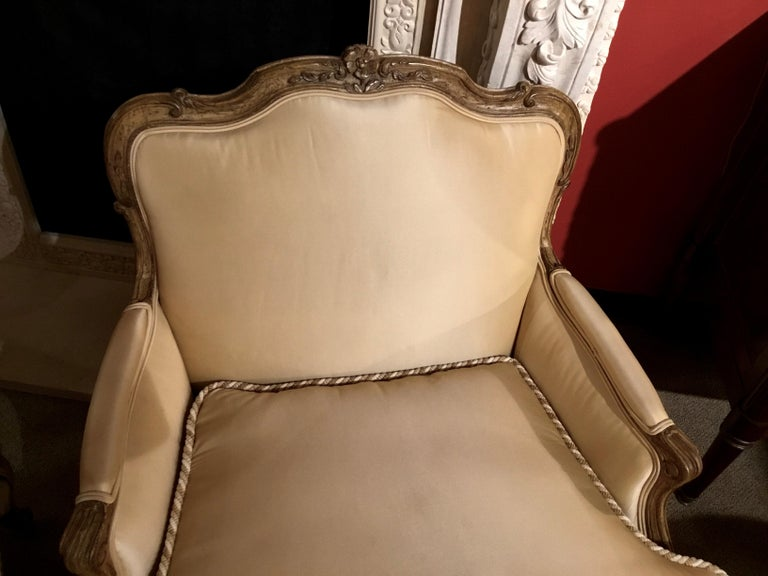 Handsome and comfortable pair of bergere Louis XV-Style chairs with floral and foliate  Carving at the crest. Painted in creamy gold hue. The back is gracefully curved and extends To a curved and nicely placed arm height. The bottom apron of these