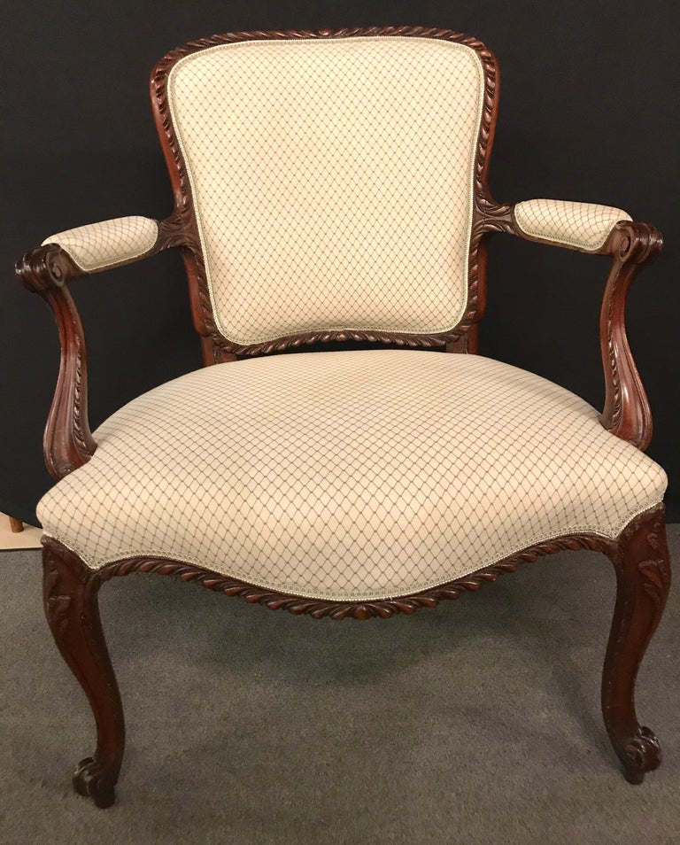 A fine pair of Louis XV style walnut fauteuils or Bergères in a Scalamandre Fabric. A simply understated pair of carved arm chairs in the finest fabric having a stripped fabric in the back with a tweed design seat and backrest.