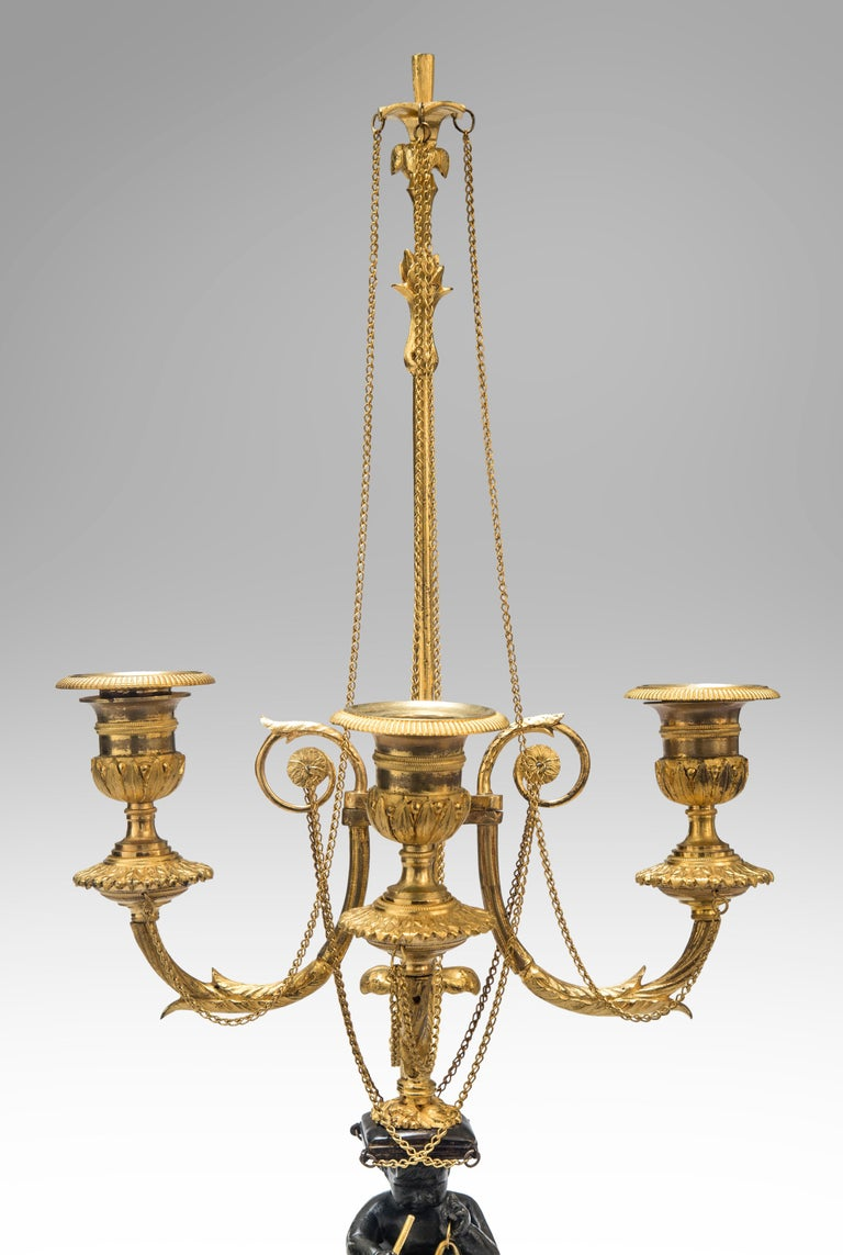 A pair of Louis XVI candelabra Late 18th century An extraordinary pair of the finest quality candelabra, crisply detailed, and with lovely gilding of a restrained yet sumptuous color. Each with a patinated bronze putto triton seated on a sleigh