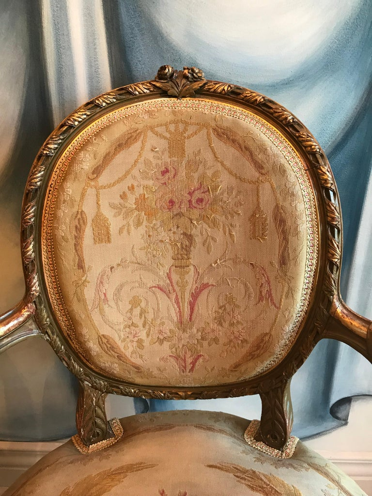 Pair of Louis XVI fauteuils, giltwood with beautifully carved details. Exquisite original gobelin fabric, the gimp has been replaced. In good condition.