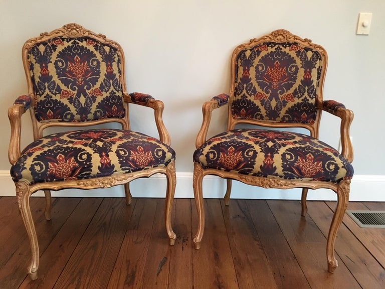 Pair of Louis XVI style armchairs covered in cut velvet fabric. Carved foliage and shell motif at the top. Very good condition. Two small ink stains on seat of one chair.