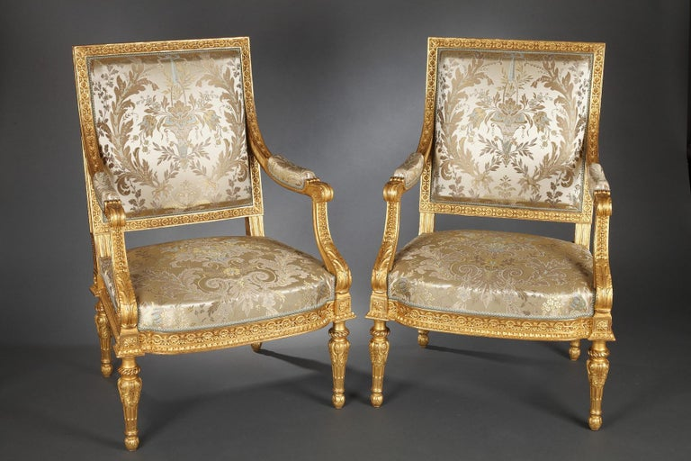 Beautiful pair of carved and gilded wood Louis XVI style armchairs. The « à la reine » backrest and the curved crosspiece are adorned with a frieze of interlacing enriched with flowers in their center, and the armrests consoles are decorated with