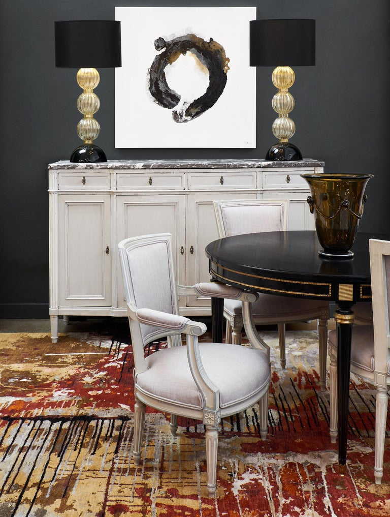 A unique, finely built pair of Louis XVI style armchairs with beautiful straight lines, slightly curved backs for comfort, and slightly tapered and hand-carved fluted legs. The chairs are nicely upholstered in a soft gray linen. We love the