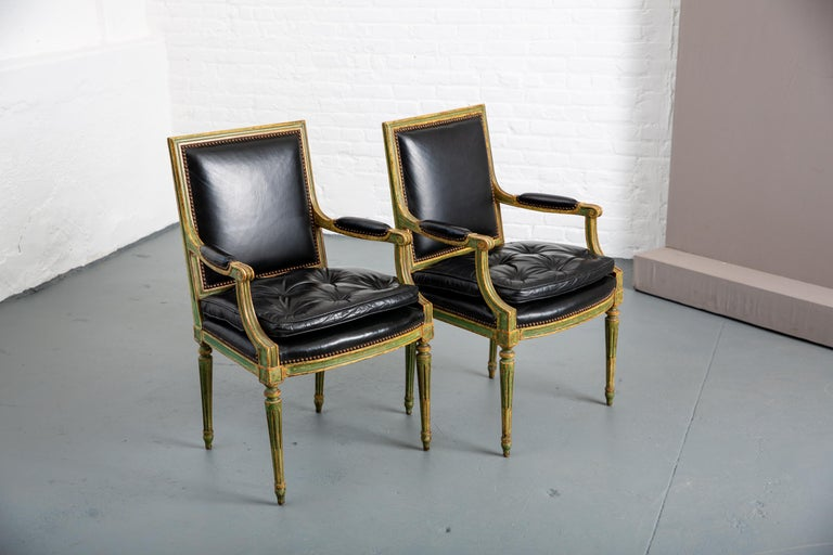 Pair of Louis XVI French carved wood leather armchairs with columnal fluted legs and nailhead trim. Great patination to green painted legs. Button tufted seat with newly refreshed double cushion.  Measures: Arm height 26.5