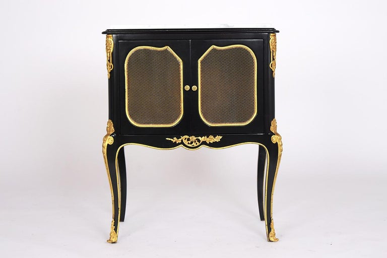 This pair of 1950s French Louis XVI style nightstands have been restored and features a newly ebonized lacquered finish. They have white Carrara marble tops, underneath it has two small doors with brass wire panels, brass knobs, and brass molded